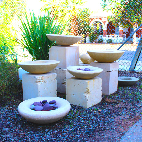 a cluster of the cement bowls sitting on blocks with a backdrop of lemongrass
