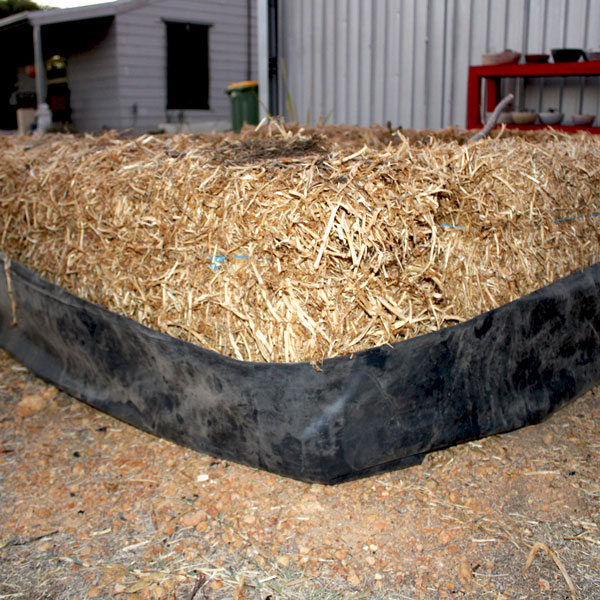 a bale of hay wrapped in black plastic, stage one of a haybale garden