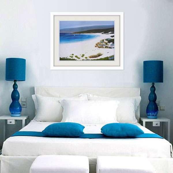 an insitue photograph of the smith beach limited edition styled in white for a bedroom interior with blue highlights  matching the azure blu colour of the sea in the picture