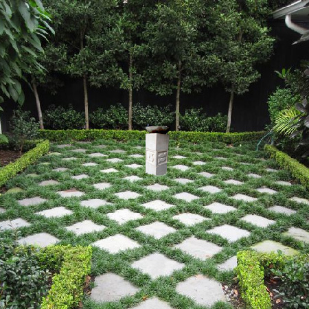 a photoshopped garden with mandys birdbath on a checkerboard patterned pavers