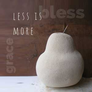 A hand sculpted cement pear by Mandy with the words - less is more
